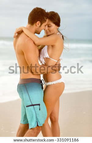 summer holidays, people, love, travel and dating concept - happy couple embracing  over sunset beach  - stock photo
