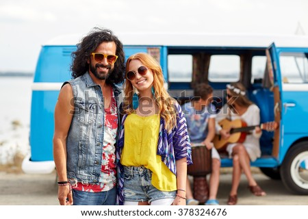 summer holidays, road trip, vacation, travel and people concept - smiling young hippie couple with friends over minivan car - stock photo