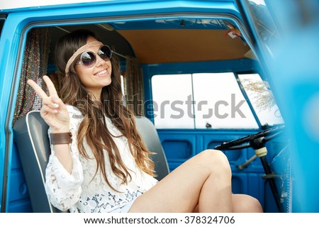 summer holidays, road trip, vacation, travel and people concept - smiling young hippie woman showing peace gesture in minivan car - stock photo