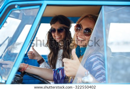 summer holidays, road trip, vacation, travel and people concept - smiling young hippie women driving and showing thumbs up gesture in minivan car - stock photo