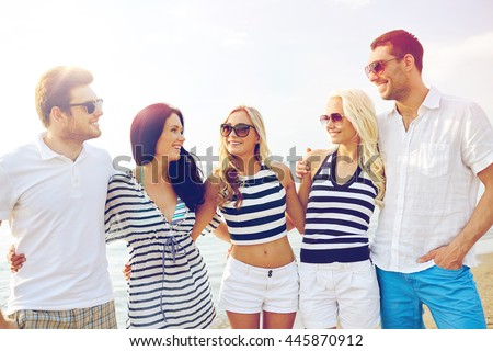 summer, holidays, sea, tourism and people concept - group of smiling friends in sunglasses talking on beach