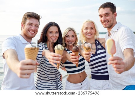 summer, holidays, sea, tourism and people concept - group of smiling friends showing ice cream on beach - stock photo