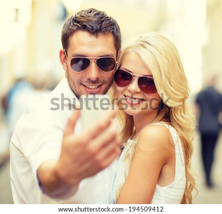 summer holidays, technology, love, relationship and dating concept - smiling couple taking picture with smartphone in the city - stock photo