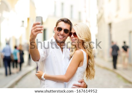 summer holidays, technology, love, relationship and dating concept - smiling couple taking selfie with smartphone in the city - stock photo