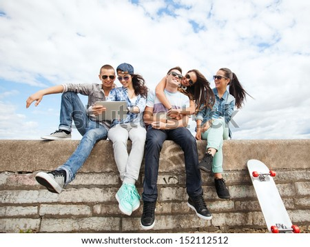 summer holidays, teenage and technology concept - group of teenagers looking at tablet pc - stock photo