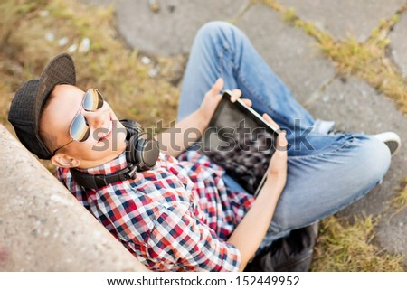 summer holidays, teenage and technology concept - teenager with headphones and tablet pc outside - stock photo