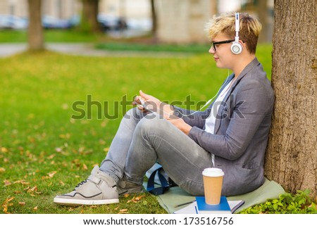 summer holidays, teenage, internet and technology concept - teenager with headphones, books, files, notebooks, coffee and tablet pc outside - stock photo