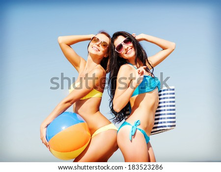 summer holidays, vacation and beach activities - girls with ball on the beach - stock photo