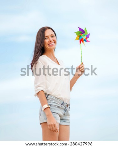 summer holidays, vacation and ecology - girl with windmill toy on the beach - stock photo