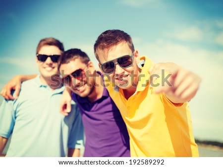 summer, holidays, vacation and happiness concept - group of friends having fun on the beach and pointing at you - stock photo