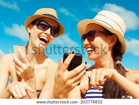 Summer, holidays, vacation and happiness concept - Pretty girls using smart phone mobile at the beach. - stock photo