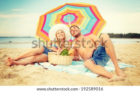 summer, holidays, vacation and happy people concept - smiling couple lying on the beach under colorful umbrella and sunbathing - stock photo