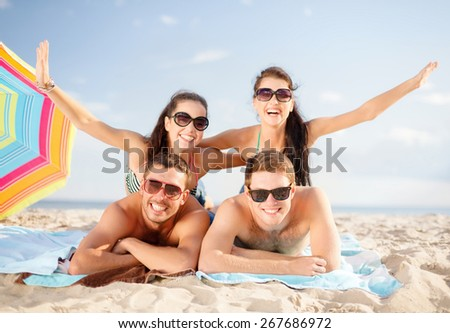 summer holidays, vacation and people concept - group of happy friends having fun and sunbathing on beach - stock photo