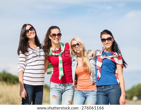 summer holidays, vacation and people concept - happy teenage girls in sunglasses or young women having fun on beach - stock photo