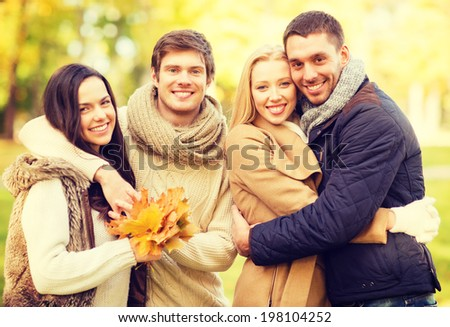 summer, holidays, vacation, happy people concept - group of friends or couples having fun in autumn park - stock photo