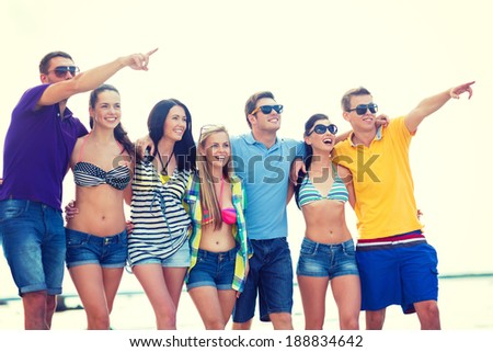 summer, holidays, vacation, happy people concept - group of friends pointing somewhere on the beach - stock photo