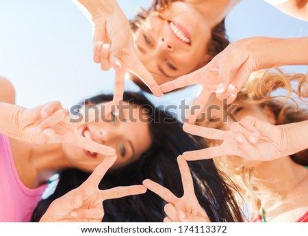 summer, holidays, vacation, happy people concept - group of girls looking down and showing finger five gesture - stock photo