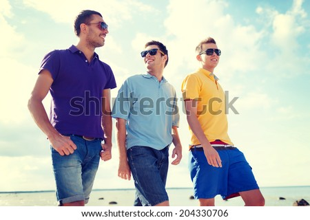 summer, holidays, vacation, happy people concept - group of male friends walking on the beach - stock photo