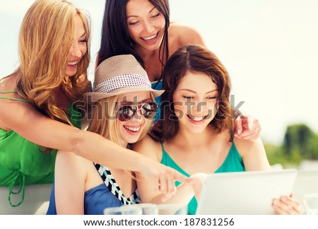 summer holidays, vacation, internet and technology - girls looking at tablet pc in cafe - stock photo