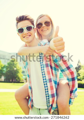 summer holidays, vacation, love, gesture and friendship concept - smiling teen couple in sunglasses having fun and showing thumbs up in park - stock photo