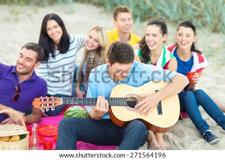 summer holidays, vacation, music, happy people concept - group of happy friends playing guitar on beach - stock photo