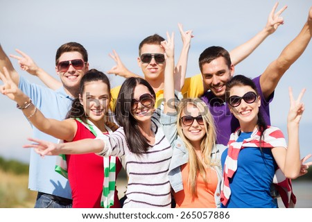 summer holidays, vacation, tourism, travel and people concept - group of happy friends having fun and showing victory gesture on beach - stock photo