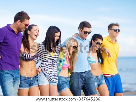 summer holidays, vacation, tourism, travel and people concept - group of happy friends walking along beach - stock photo
