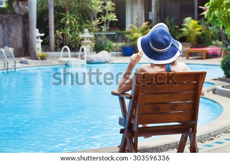 summer holidays, woman relaxing in beautiful luxury hotel near swimming pool - stock photo
