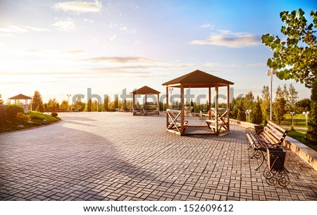 Summer houses with benches at sunset sky background in dendra park of first president Nursultan Nazarbayev in Almaty, Kazakhstan - stock photo