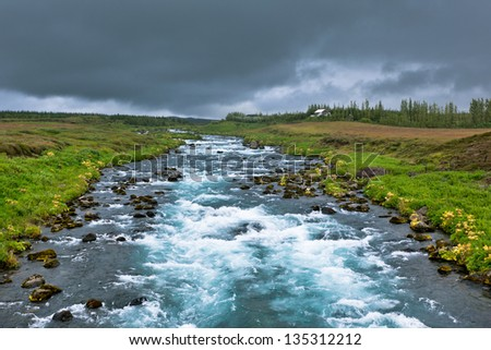 Summer Iceland Landscape with Raging River at Overcast Weather - stock photo
