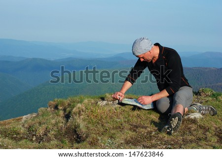Summer in the Carpathian Mountains. Hiker sitting on top, looking at the map - stock photo