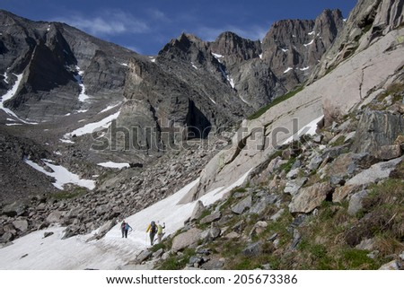 Summer in the Colorado Rockies - Hikers in a snow field on the Chasm Lake trail near Longs Peak. - stock photo