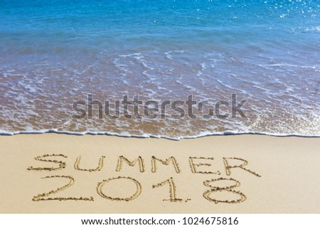 Summer 2018 inscription on wet beach sand and sea wave on background. Summer season holiday, vacation concept.