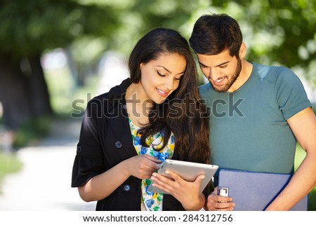 summer, internet, education, campus and teenage concept - students or teenagers with tablet computers hanging out - stock photo