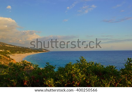 Summer Ionian Sea coastline view with sandy beach on the sunset with green bushes in front, Albania - stock photo