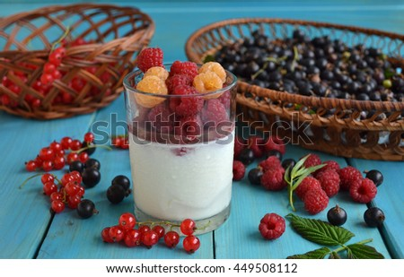Summer is time for cold dessert with fresh berries. Yogurt in a glass cup with red and yellow raspberry, wicker baskets with red and black currants are on the blue wooden table. Healthy fitness food.  - stock photo