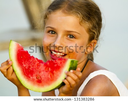 Summer joy, lovely girl eating fresh watermelon on the beach, happy child concept
