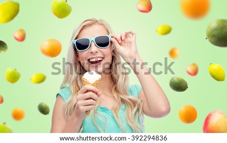summer, junk food and people concept - young woman or teenage girl in sunglasses eating ice cream over green background with fruits - stock photo