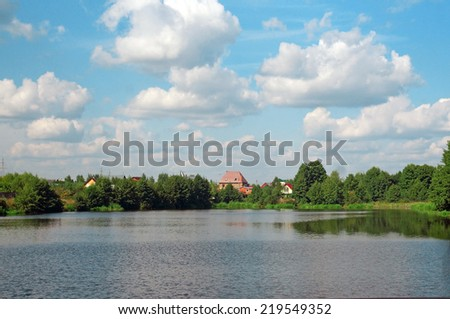 Summer landscape: houses hiding behind trees on the shore of the lake under a blue sky with white clouds                                - stock photo