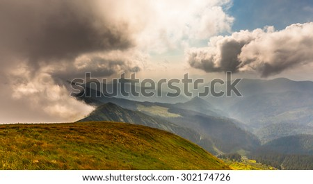 Summer landscape in mountains and the dark blue sky with clouds.