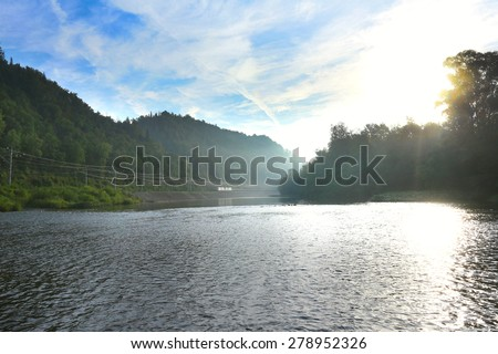 summer landscape misty morning on the river in the Ural Mountains and the railroad along the shore - stock photo