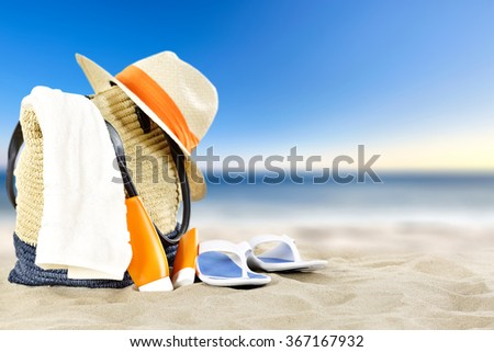 summer landscape of beach and blue sky with hat and bag and shoes