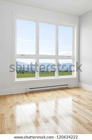 Summer landscape seen through the big window of an empty room. - stock photo