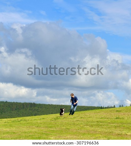 Summer landscape. Sky, clouds, space, running young man and dog - stock photo