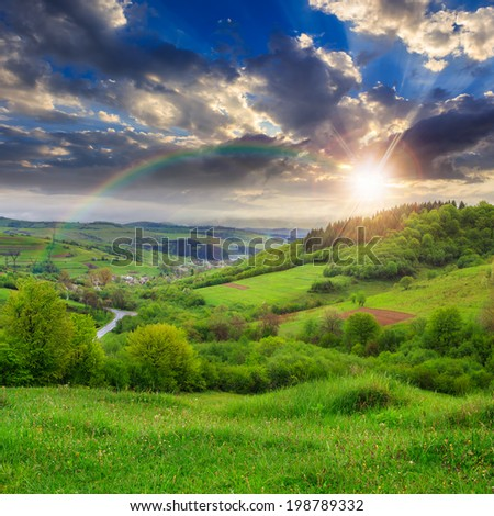 summer landscape. village on the hillside. forest on the mountain light fall on clearing on mountains at sunset with rainbow