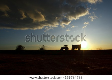 Summer landscape with a field and a tractor on a road - stock photo