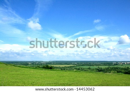 Summer landscape with a wide green valley and the blue sky with white clouds.