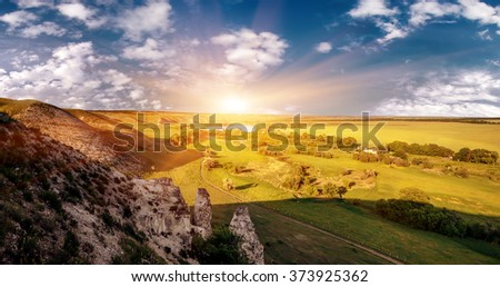 summer landscape with chalk mountain, flowers and cloudy sky on sunset, natural  background