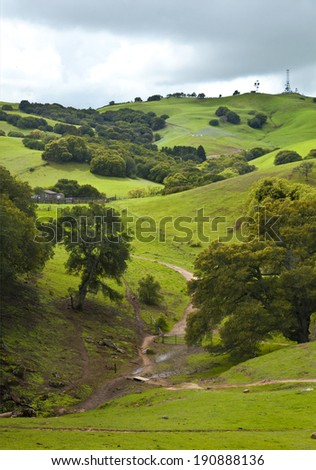 Summer landscape with cloudy sky, green hills and dirt road. Nature background - stock photo