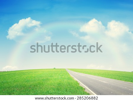 Summer landscape with endless asphalt road through the green field and blue sky with rainbow - stock photo
